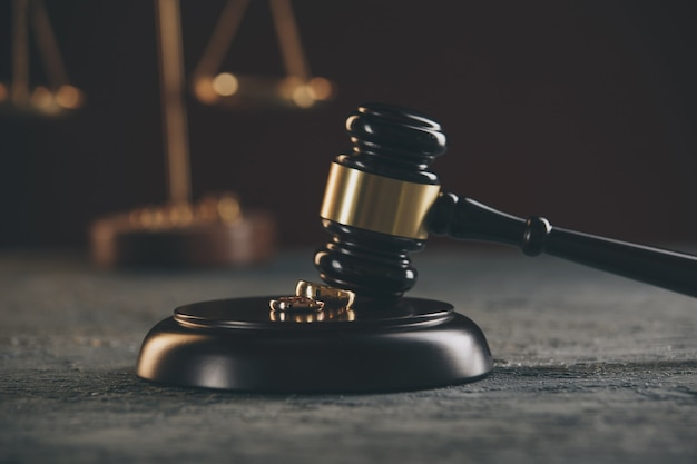Trouwringen op de figuur van een gebroken hart van een boom, hamer van een rechter op een houten achtergrond. echtscheidingsprocedures