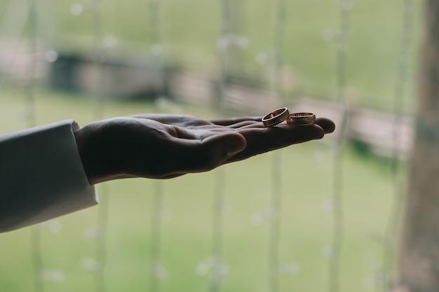 Trouwringen op de palm van de bruidegom close-up