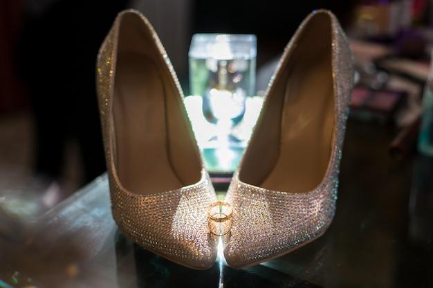 Trouwringen op de schoenen van de bruid.
