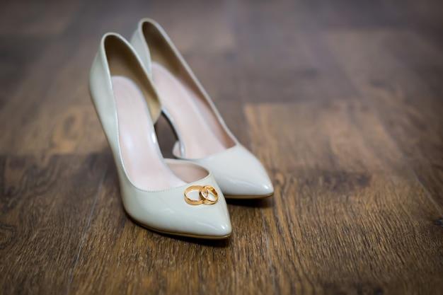 Trouwringen op de schoenen van de bruid