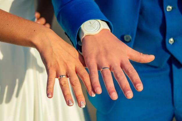 Trouwringen op de vingers van de bruid en bruidegom. concept van een huwelijksceremonie op het strand.