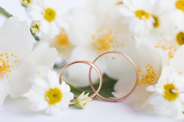 Trouwringen op een witte achtergrond. feestelijke verlovingssieradenset