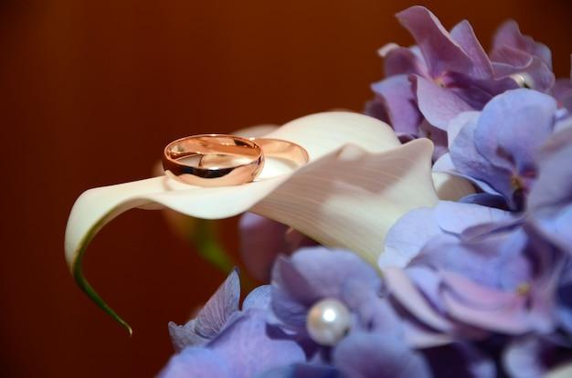 Trouwringen op een witte bloem van een mooie bruid boeket