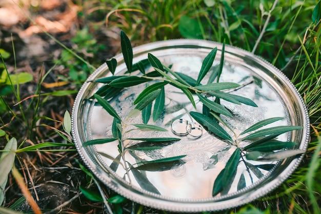 Trouwringen op een zilveren dienblad met olijftakken trouwjuweel