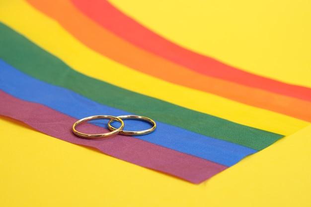 Trouwringen op lgbt-vlag, gele achtergrond, exemplaarruimte
