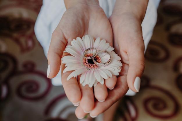Trouwringen op mooie bloem in vrouwen zachte handen binnen