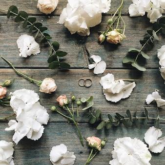 Trouwringen, rozen, witte hortensia's en takken geïsoleerd op oude retro houten munttafel