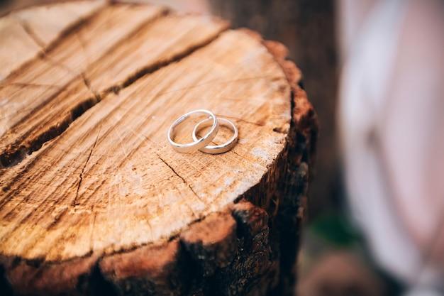 Trouwringen. sieraden in wit en geel goud. trouwring op de houten textuur. houten stomp
