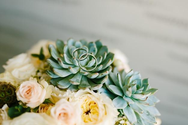 Trouwringen van de bruid en bruidegom op de echeveria-bloem in het bruidsboeket van de bruiden