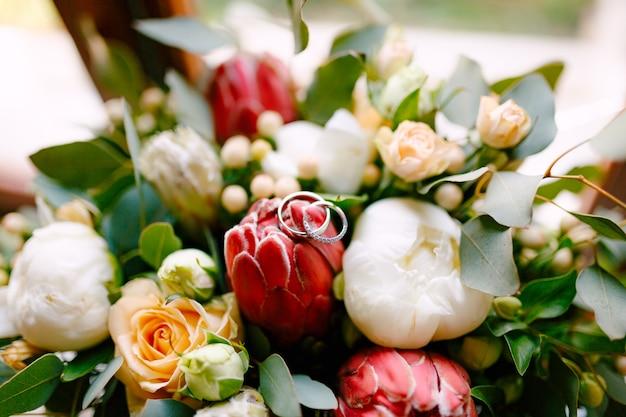 Trouwringen van de bruid en bruidegom op een knop in een boeket rozen en pioenrozen in rood en wit