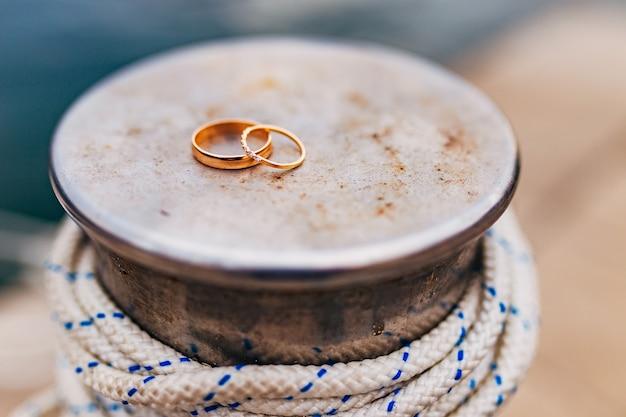 Trouwringen van de pasgetrouwden in de buurt van de zee. gouden verlovingsringen. bruiloft in montenegro.