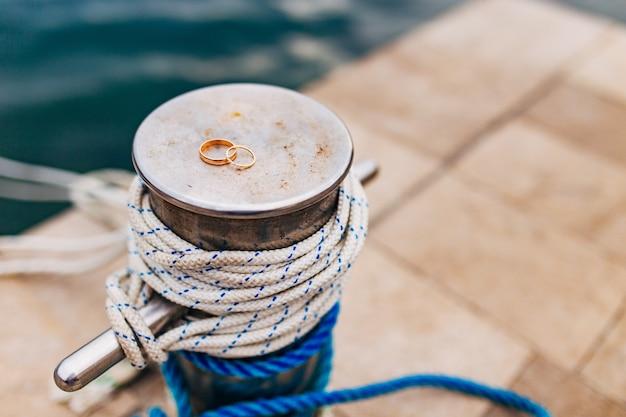 Trouwringen van de pasgetrouwden in de buurt van de zee gouden verlovingsringen