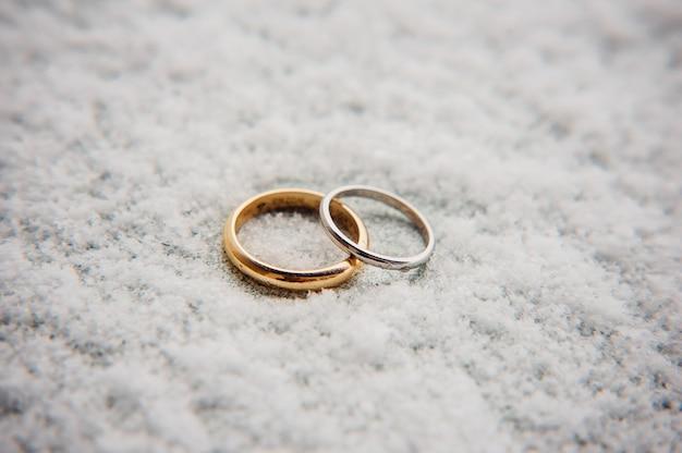 Trouwringen van pasgetrouwden in de sneeuw gouden verlovingsringen