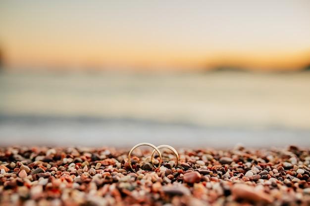 Trouwringen van pasgetrouwden op strand kiezelstenen