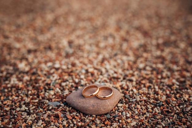 Trouwringen van pasgetrouwden op strandkiezels