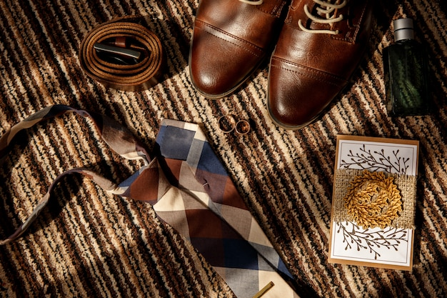 Trouwringen voor bruid en bruidegom op smartphone in de buurt van schoenen voor bruidegom, lederen riem, parfumfles en stropdas in rustieke stijl