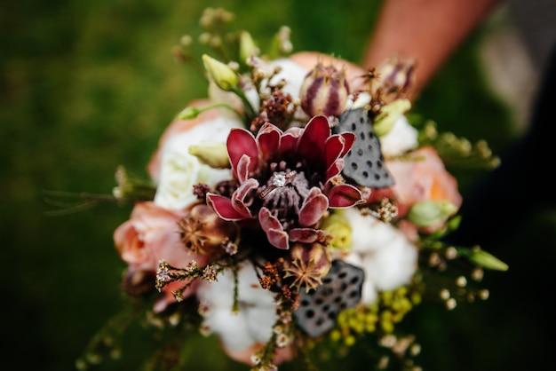Trouwringenclose-up op een mooi huwelijksboeket tijdens zonsondergang. bruiloft accessoires.