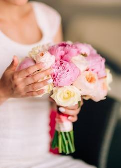 Trouwrozen en pioenrozen in de handen van de bruid bruiloft