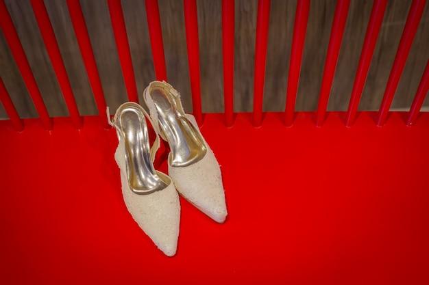 Trouwschoenen en boeket op een rode stoel voor de bruiloft ceremomy