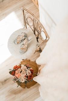 Trouwschoenen en huwelijksboeket op de stoel