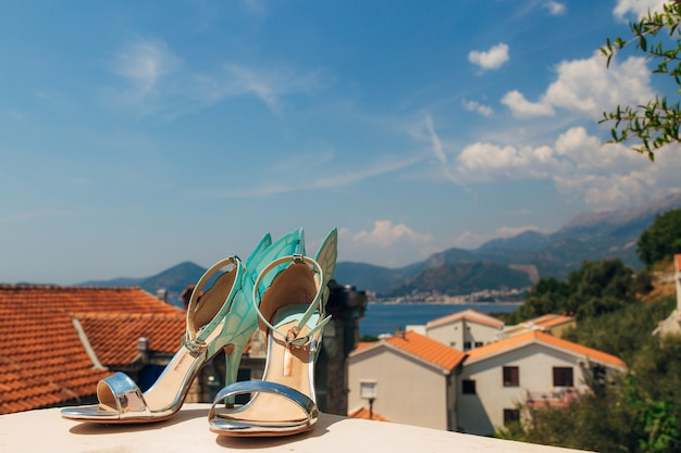 Trouwschoenen van de bruid tegen de achtergrond van bergen en de zee