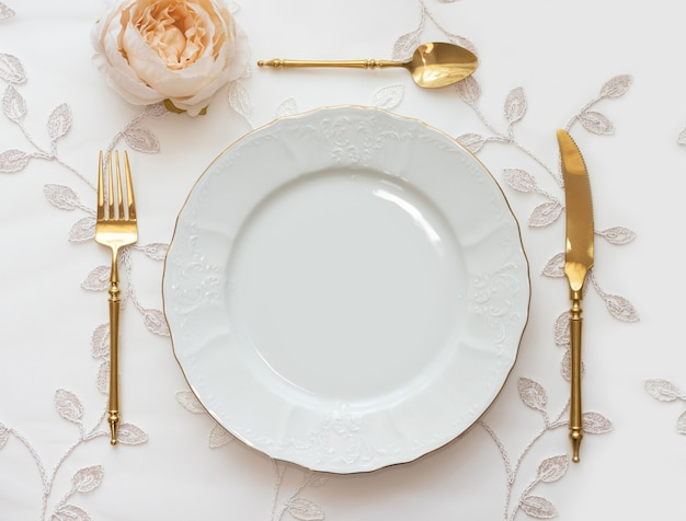 Trouwtafel ingericht met gouden bestek en witte opladerplaat