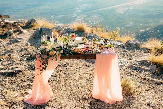 Trouwtafel versierd met bloemen en stof in de vorm van een trein en geserveerd met lekkernijen in