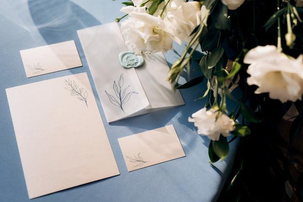 Trouwuitnodiging in een blauwe envelop op een tafel met groene takjes