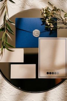 Trouwuitnodiging in een grijze envelop op een tafel met groene takjes