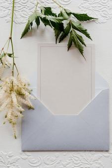 Trouwuitnodiging in een grijze envelop op een tafel met groene takjes Premium Foto