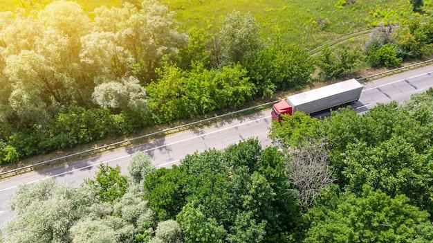 Truck logistieke antenne. wagen rijden langs de rijbaan tussen groen bos.