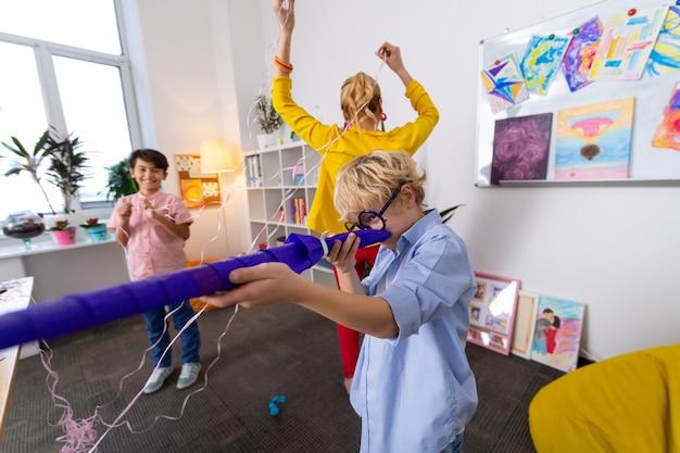 Trucs spelen. leraar en twee knappe slimme schooljongens die trucjes uithalen na leuke kunstles