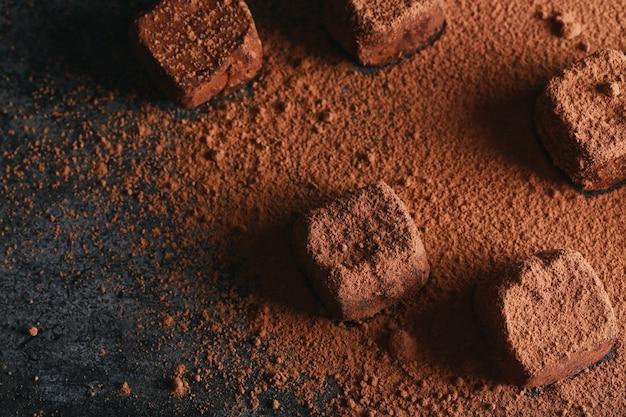 Truffel besprenkeld met cacao. donker chocoladesuikergoed in cacaopoeder op een donkere bruine achtergrond