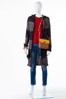 Trui jas en tweekleurige portemonnee. mannequin in bovenkleding met tas. bruin en geel lederen handtas. accessoirekeuze voor herfstoutfit.
