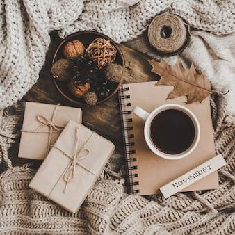Truien en kopje thee met notebook, kaars en breikleding
