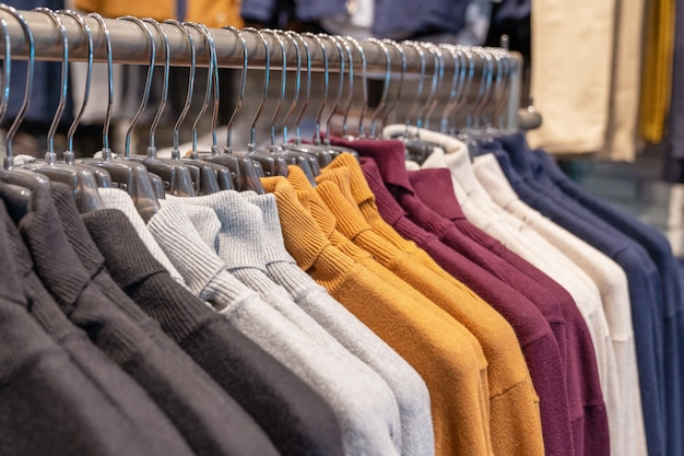 Truien en pullovers in verschillende kleuren, zwart, grijs, wit en karmozijnrood hangen aan een hanger in een kledingwinkel op een rij. herfst- en wintercollectie