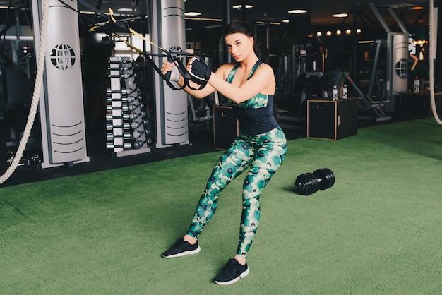Trx-concept. mooie dame die haar spieren met behulp van de slinger van de ophangingstrainer of ophangingsriemen in gymnastiek uitoefenen