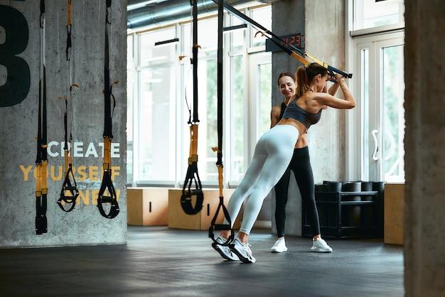 Trx-training. jonge atletische vrouw in sportkleding die traint met fitnessriemen met hulp van een persoonlijke trainer in de sportschool. sport, training, wellness en een gezonde levensstijl