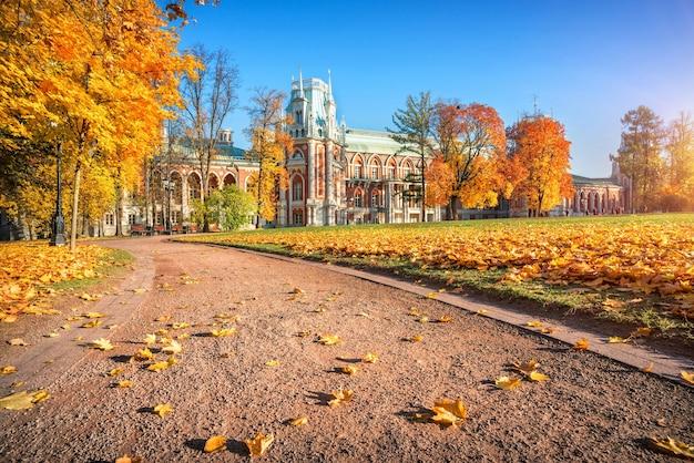 Tsaritsyno palace in moskou, omgeven door kleurrijke herfstbomen van het park en bladeren op een pad in de ochtendzon