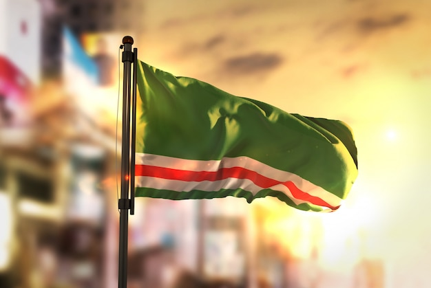 Tsjetsjeense republiek ichkeria vlag tegen stad wazige achtergrond bij zonsopgang achtergrondverlichting