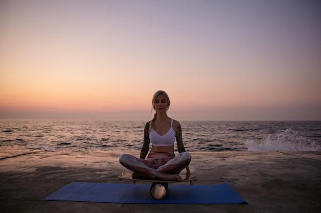 Tslim blonde vrouw zittend op een balansbord met gesloten ogen en kalm gezicht, poseren over zeezicht tijdens zonsopgang, helpen om het evenwicht te bewaren met de handen