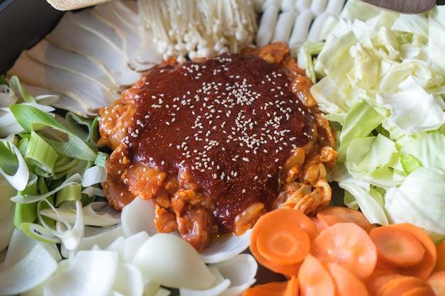 Tteok-bokki (koreaanse traditionele gerechten warme en pittige rijstwafel), combinatie en breng bladerdeeg met kaas en groente op de zwarte tafel