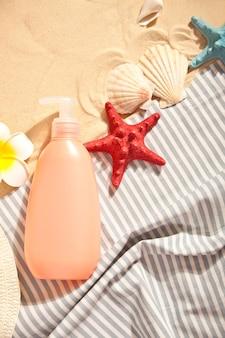 Tube zonnebrandcrème, zeesterren, plumeria frangipani en schelpen