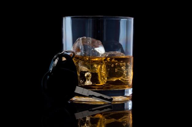 Tuimelglas met whisky en een autosleutel