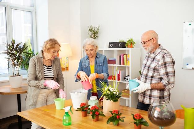 Tuinclub. leuke gezellige mensen die samen bloemen planten terwijl ze genieten van het tuinieren