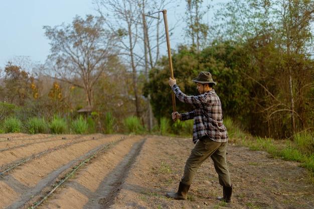Tuinconcept een mannelijke boer die een schoffel gebruikt die in de grond graaft voor het maken van moestuinen die zich voorbereiden op het kweken van de planten.