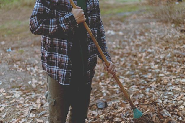 Tuinconcept een mannelijke tuinman die een kokosbladbezem gebruikt om de droge gevallen bladeren te verzamelen om het gebied schoon te maken.