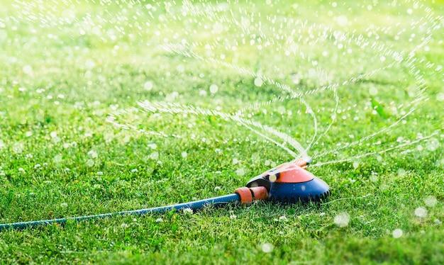 Tuingazonsproeier die water over het gras sproeit.