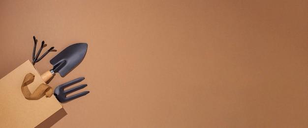 Tuingereedschap in een cadeauzakje op een bruine achtergrond. bovenaanzicht, plat gelegd. banier.