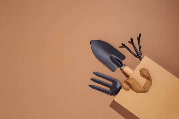 Tuingereedschap in een cadeauzakje op een bruine achtergrond. bovenaanzicht, plat gelegd.